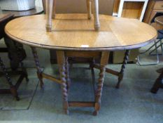 An early 20th century oak oval topped drop leaf table