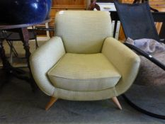 A modern armchair upholstered in an olive fabric on beech legs