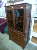 An early 20th century oak record cabinet with glazed doors enclosing fitted shelving over two