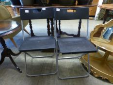 A pair of black PVC and tubular metal folding chairs
