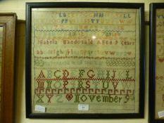 A framed and glazed sampler by Isabella McDonald aged nine