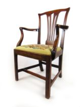 An 18th century mahogany open arm chair with needle work upholstered seat, h. 98 cm, w. 61 cm, d.