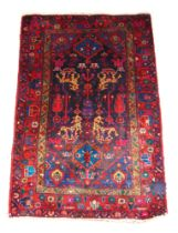 A handwoven Persian rug, the triple line border enclosing the field with animal motif's,