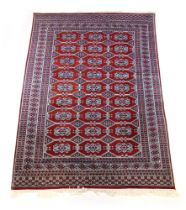 A handwoven Indian rug, the multi line border enclosing a red ground field with octagons,