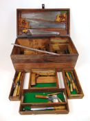 An early 20th century pine tool chest containing a selection of hand tools to include saws, chisels,