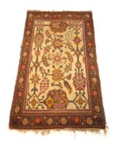 A handwoven Turkish rug, the main floral border surrounding a cream ground field with floral motifs,