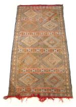 A handwoven Moroccan rug, the border surrounding a segmented geometrical field,
