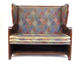 A late 19th century walnut settle with floral carved sides upholstered in a patterned fabric, h.