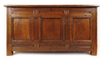 An early 18th century oak coffer, the four panel top over a three panel front, h. 72 cm, w.
