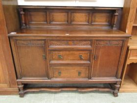 An early 20th century oak sideboard having three drawers flanked by cupboard doors