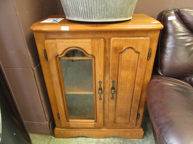 A modern cabinet having a glazed door and a solid door