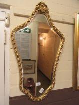 An ornate gilt framed bevel glass mirror