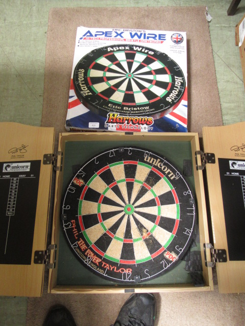 A boxed dart board together with another dart board in case