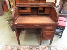 An early 20th century oak roll top desk