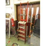 A set of red metal stepladders together with a set of wooden stepladders