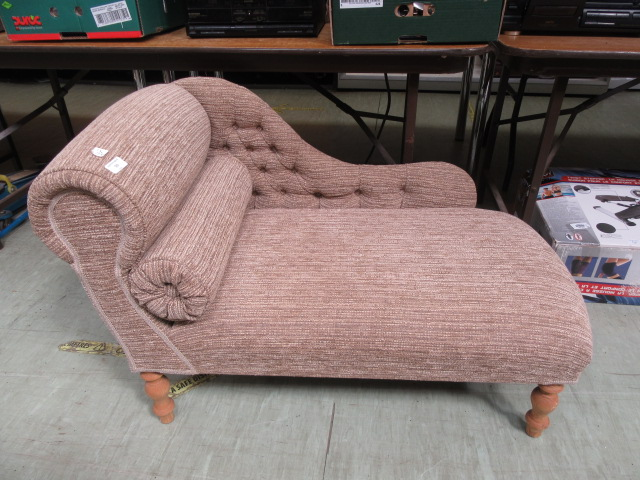 A modern small scale chaise lounge upholstered in a cut button back fabric