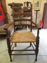 An early 20th century oak framed open armchair with seagrass seat