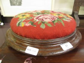 A Victorian walnut footstool with floral needlework upholstery