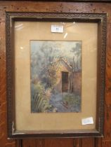 A framed and glazed watercolour of an outhouse