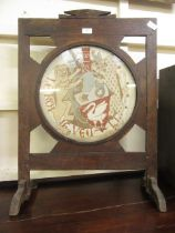 An early 20th century oak firescreen with armorial needlework panel
