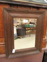 An early 20th century oak framed mirror