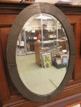An early 20th century hammered pewter framed oval bevel glass mirror