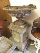 A composite stone garden urn on plinth