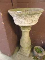 A weathered stone planter on plinth