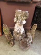 Four composite stone garden ornaments of gnomes, children,
