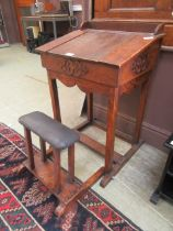 An early 20th century oak school desk with fold out seat and lift up slope