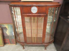 An early 20th century walnut veneered display cabinet incorporating clock to top center