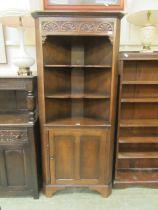 A reproduction oak floor standing corner cupboard