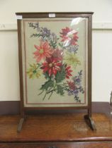 A framed and glazed early 20th century firescreen having a woolwork under glass to center