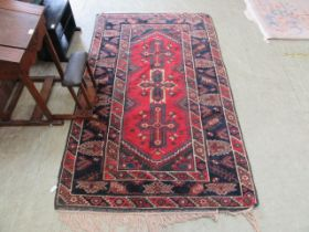 A hand woven north Persian rug triple line border enclosing a red ground field