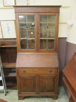 An early 20th century bureau bookcase, two lead glass doors over fall front, single drawer,