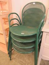 A set of four green metal garden chairs