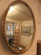 An oval gilt framed wall mirror