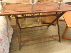 A stained folding wooden garden table