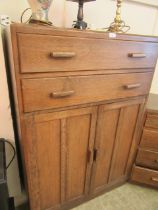 A mid-20th century tall boy having two drawers above two cupboard doors together with a matching