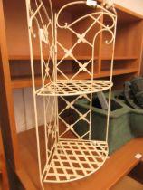 A cream painted white metal corner shelf unit