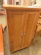 A modern oak two door cabinet concealing shelving
