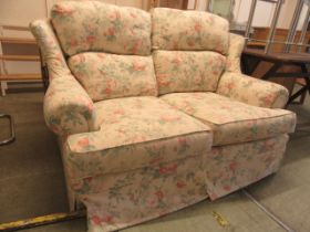 A two seat wing back settee upholstered in a rose fabric