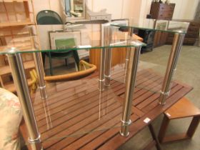 A pair of modern glass and brushed chrome legged occasional tables