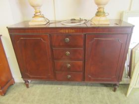 A modern mahogany and brass inlaid sideboard with four central drawers flanked by cupboard doors