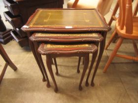 A nest of three mahogany effect and tooled leather topped tables