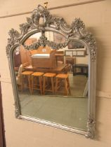 A silver painted ornate framed over mantle mirror