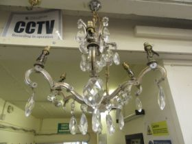 An early 20th century six branch brass and cut glass ceiling hanging chandelier