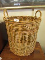 A wicker twin handled laundry basket
