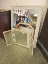 An ornate cream framed bevel glass mirror along with a triple vanity mirror and one other