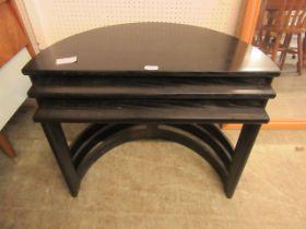 A nest of three black ash demi-lune tables